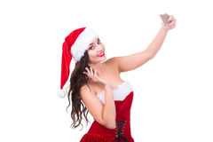 Portrait of beautiful young woman wearing santa claus clothes with smartphone making selfie. Isolated on white. Portrait of beautiful sexy girl wearing santa Stock Images