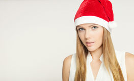 Portrait of beautiful young woman wearing santa claus hat Stock Photos