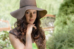 Portrait of beautiful young woman wearing sunhat in park stock image