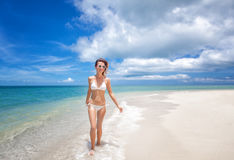 Portrait of a beautiful young woman in a white bikini walking al Royalty Free Stock Photos