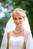 Portrait of beautiful young woman in white dress walking in park Stock Photos