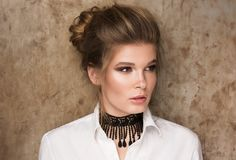 Portrait of a beautiful young woman in a white shirt with a black choker on her neck. Professional Nude-makeup. Perfect clean skin. Hair in a bun. Metal wall stock photos