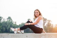 Portrait of beautiful young woman in white t-shirt and black trousers sitting in nature at sunset. Student life stock photography