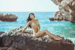 Portrait of beautiful young woman on wild rocky beach. Romantic passion young girl in bikini outdoors against wild tropical sea background. Portrait of Royalty Free Stock Image
