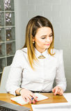 Portrait of beautiful young woman working in her office. Royalty Free Stock Photos