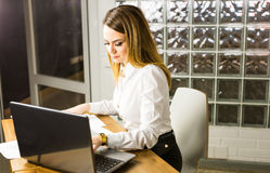 Portrait of beautiful young woman working with laptop in her office. Royalty Free Stock Photos