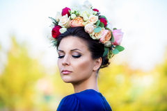 Portrait of a beautiful young woman in a wreath of roses, outdoo Royalty Free Stock Photos