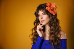 Portrait of a beautiful young woman on a yellow background, beautiful flower in her hair, delicate natural make-up royalty free stock photo