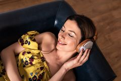 Portrait of a woman while listening to music on a sofa. Portrait of a beautiful young woman in a yellow dress while listening to music and lying on a sofa royalty free stock photography