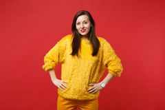 Portrait of beautiful young woman in yellow fur sweater standing with arms akimbo isolated on bright red wall background. In studio. People sincere emotions stock photos