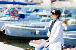 Portrait of a beautiful woman sittin ont he pier near fishing boats. Happy girl in sunglasses. Summer sunny day stock image