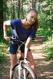 Portrait of a beautiful young women with a bicycle on park background Stock Photos