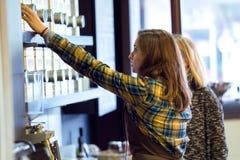 Beautiful young woman customer choosing tea sold by weight in organic shop. stock image