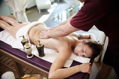 Young Woman Enjoying Massage in SPA. Portrait of beautiful young women lying on massage table with eyes closed and smiling enjoying SPA treatment, men massaging Royalty Free Stock Photography