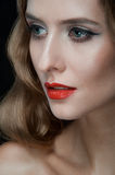 Portrait of beautiful young women with red lips. Portrait of amazing young girl with red lips, wavy hair, black eyeliner. Beauty. Studio shot. Black background Stock Images