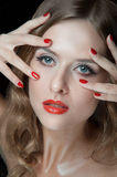 Portrait of beautiful young women with red lips. Portrait of amazing young girl with red lips, wavy hair, black eyeliner. Beauty. Studio shot. Black background Royalty Free Stock Image