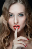 Portrait of beautiful young women with red lips. Portrait of amazing young girl with red lips, wavy hair, black eyeliner. Beauty. Studio shot. Black background Royalty Free Stock Photos