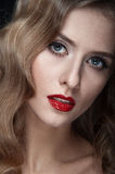 Portrait of beautiful young women with red lips. Portrait of amazing young girl with red lips, wavy hair, black eyeliner. Beauty. Studio shot. Black background Stock Photo