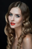 Portrait of beautiful young women with red lips. Portrait of amazing young girl with red lips, wavy hair, black eyeliner. Beauty. Studio shot. Black background Royalty Free Stock Photo