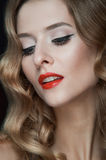 Portrait of beautiful young women with red lips. Portrait of amazing young girl with red lips, wavy hair, black eyeliner. Beauty. Studio shot. Black background Royalty Free Stock Images