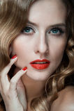 Portrait of beautiful young women with red lips. Portrait of amazing young girl with red lips, wavy hair, black eyeliner. Beauty. Studio shot. Black background Royalty Free Stock Photography