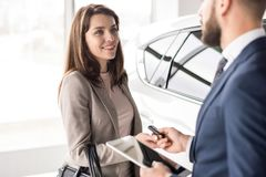 Car Salesman Working with Client. Portrait of beautiful young women taking keys form car salesman standing next to white shiny luxury car in dealership showroom Royalty Free Stock Image
