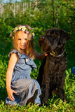 Portrait of beautifull girl and her black dog. Portrait of beautifull girl and her black dog at the sunlight royalty free stock photography