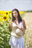 Portrait of a beautifull girl near sunflower field. With a big hat Stock Photo