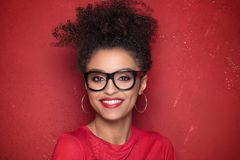 Portrait of beauty afro girl with toothy smile. Portrait of smiling beautiful african american young woman. Girl with afro wearing eyeglasses. Red background Royalty Free Stock Photo