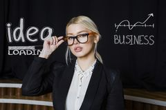 Portrait of a beauty blond busiensswoman in a black suit standing near white sketchs. Portrait of a young beauty blond busiensswoman in a black suit standing Royalty Free Stock Image