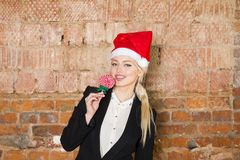 Portrait of beauty business woman with lolipop and santa hat wearing. Brick red background. Portrait of beauty blond business woman with lolipop and santa hat Royalty Free Stock Photos