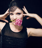 Portrait of beauty blond woman with roses in her mouth Royalty Free Stock Photo
