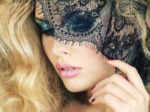 Portrait of beauty blond young woman through lace close up. stock photography