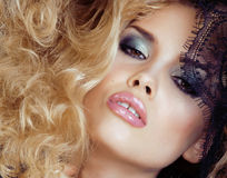 Portrait of beauty blond young woman through black lace close up sensual seduction Stock Photography
