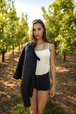Portrait of beauty brunette standing in green scenery of fruit orchard, she keep leather jacket on arm, all lit by warm sunset. royalty free stock images