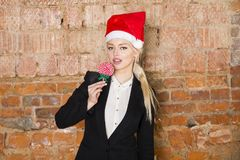 Portrait of beauty business woman with lolipop and santa hat wearing. Brick red background. Portrait of beauty blond business woman with lolipop and santa hat Stock Photos