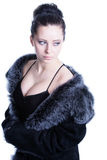 Beautiful brunette with decollete in luxury black color fur coat looking away Stock Photos
