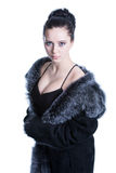 Beautiful brunette with decollete in luxury black color fur coat Royalty Free Stock Photography