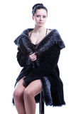 Beautiful woman with decollete in luxury fur coat sitting Stock Images