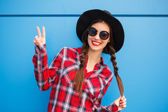 Portrait of beauty fashion smiling woman with braid hairstyle, making peace by fingers in sunglasses on blue background royalty free stock photography