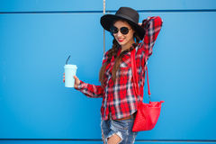 Portrait of beauty fashion smiling woman with coffee in sunglasses on blue background. Outdoor. Copyspace Stock Photography