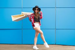 Portrait of beauty fashion smiling woman with shopping bags in sunglasses on blue background. Outdoor. Copyspace Stock Image