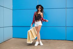 Portrait of beauty fashion smiling woman with shopping bags in sunglasses on blue background. Outdoor. Copyspace Stock Photo