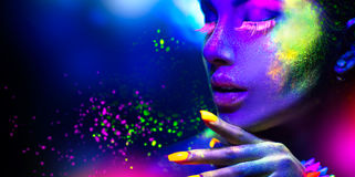 Portrait of beauty fashion woman in neon light. Fashion woman in neon light, portrait of beauty model with fluorescent makeup royalty free stock photos