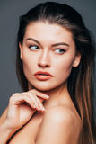 Portrait of beauty girl with beauty skin, touch body with hands on grey background. Cosmetics or spa, healtcare concept. Royalty Free Stock Photography