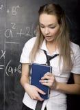 Portrait of beauty happy student with books near blackboard Stock Photo