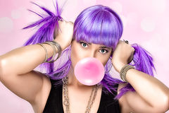 Beauty Party Girl. Purple Wig and Pink Bubble Gum. Portrait of beauty party girl with purple wig and pink bubble gum stock image
