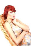 Portrait of beauty red hair female model sitting. On wicker chair - made in studio on white background Stock Photography