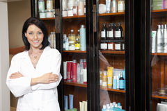Portrait of a beauty salon employee standing with arms crossed and cosmetics in background Stock Images