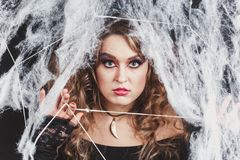 Portrait of Beauty Witch girl caught in a spider web. Fashion Art design. Beautiful Gothic model girl with. Halloween make up and costume. Close-up shot royalty free stock photography